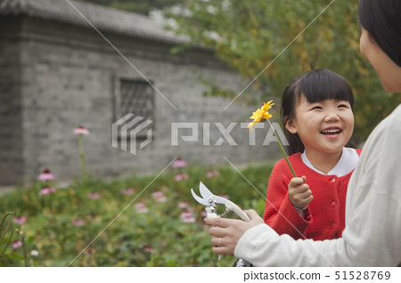 Smiling young girl with flower 51528769