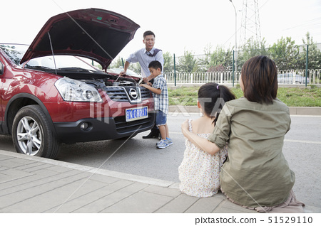 Mother and Daughter Watch as Father and Son Try to Fix the Car 51529110