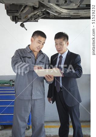 Mechanic Explaining to Businessman 51529232