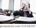 Young businesswoman sitting at desk covering her face with a paper 51536267