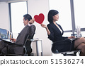 Work romance between two business people holding a heart 51536274