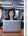 Young businesswoman sitting in front of laptop, portrait 51536279