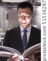 Young smiling businessman reading a book 51536287