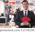 Businessman holding red envelopes and coworkers hanging decorations for Chinese 51536295