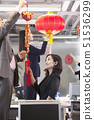 Coworkers hanging decorations in office for Chinese new year 51536299
