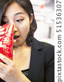 Young businesswomen looking into traditional red envelopment, Chinese New Year 51536307