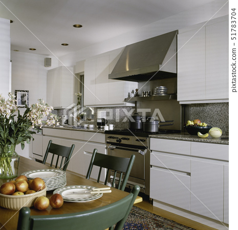KITCHEN ;  with  partial table showing to left with green chairs, and granite counters, stainless st 51783704