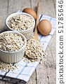 Oat flakes in ceramic bowls and wooden spoon and 51785646