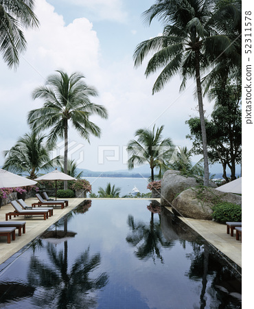Hotel resort with sun loungers beside swimming pool 52311578