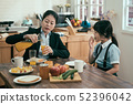 young woman mother pour fresh orange juice 52396042