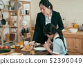 woman standing by table with girl eating toast 52396049