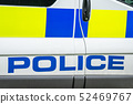 Fragment of a white police car with a word POLICE spelled out in blue in England , close up 52469767