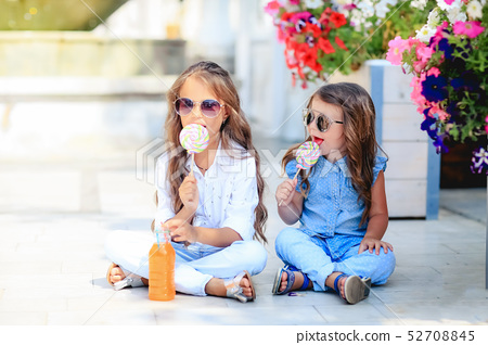 A Two cute little sisters eating huge lollipops outdoors on beautiful summer day. 52708845