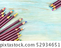 Many various color pencils forming a frame, shot from above on a teal blue background with a place 52934651