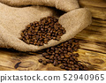 Roasted coffee beans on sackcloth on wooden table 52940965