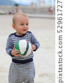Cute Baby Holding a Soccer Ball on Sand 52961727