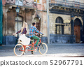 Young tourist couple, handsome man and pretty blond woman riding tandem bicycle along city street. 52967791