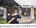 woman holding smartphone and looking at wristwatch 52968100