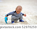 Baby Boy Playing With Sand And Blue Plastic Shovel 52970250