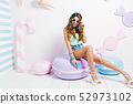 Glad slim girl with long legs sitting on big purple macaroon and laughing. Indoor portrait of pretty 52973102