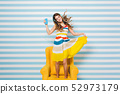 Optimistic girl wearing tn colorful dress chilling in yellow armchair and listening relaxing music 52973179