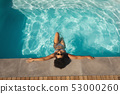 Young mixed-race woman with sunglasses leaning on edge of pool 53000260