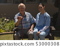 Front view of young female doctor and senior man looking at camera while sitting on bench 53000308