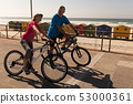 Senior couple riding a bicycle on a promenade at beach 53000361