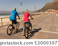 Senior couple riding a bicycle on a promenade at beach 53000397
