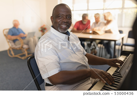 Senior man playing piano at nursing home 53000436