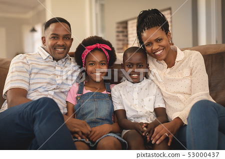Happy African American family sitting on the sofa and looking at camera 53000437