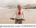 Senior woman riding a bicycle on the beach 53000656