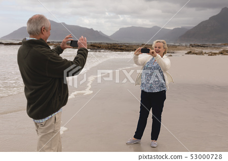 Senior couple taking photo of each other with mobile phone at the beach 53000728