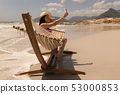 Woman taking selfie with mobile phone while relaxing on hammock 53000853