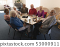 Front view of happy group of senior friends sitting on dining table and looking at camera 53000911