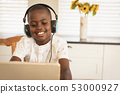 African American boy playing game on digital tablet at dining table in kitchen 53000927