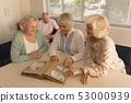 Group of senior women looking at photo album at nursing home 53000939