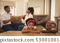 African American children leaning on table while parents arguing on the sofa 53001001