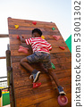 Schoolboy climbing a wall in the school playground 53001302