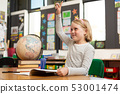 Schoolgirl raising her hand at desk in the classroom 53001474