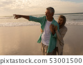 Senior man with senior woman pointing at distant on the beach 53001500