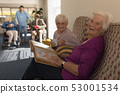 Side view of senior women with photo album looking at camera in home 53001534