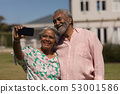 Senior couple taking selfie with mobile phone in the backyard 53001586