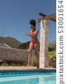 Woman in bikini walking near swimming pool 53001654