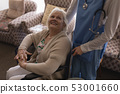 Female doctor interacting with disabled senior woman in living room 53001660