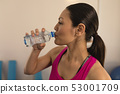 Side view of beautiful young woman drinking water after workout 53001709