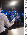 Businessman giving presentation in front of audience in auditorium 53001813