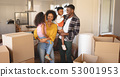 Happy African American parents with their children and boxes moving in new house 53001953