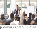 Businessman speaking at business seminar with business people raising their hands 53002141