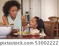 African American mother cleaning her daughter mouth with napkin at dining table 53002222